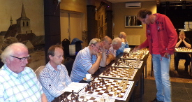 Als een grootvorst schreed clubkampioen Stan Heijmans langs de 15 borden om met ieder te delen in de lusten en lasten van de mooiste sport op aarde, voortbewogen door de kracht van het schaakgenoegen, van enkele pilsjes en van één enkele sigaret. Over de score van 40% was hij niet helemaal tevreden maar wel content met deze simultaan als feestelijk openingsritueel van het nieuwe schaakseizoen.
